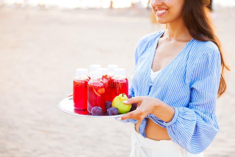 Den lyckliga kvinnan rymmer en maträtt med en röd fruktsaft för drinkar på solnedgången Picn royaltyfria bilder