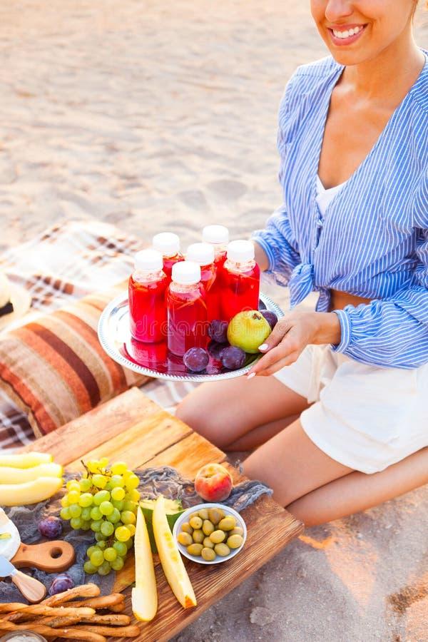 Den lyckliga kvinnan rymmer en maträtt med en röd fruktsaft för drinkar på solnedgången Picn fotografering för bildbyråer