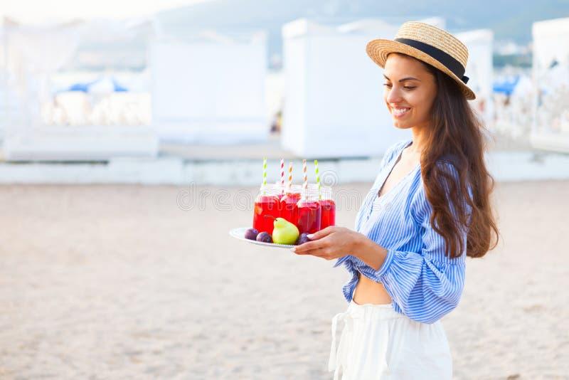 Den lyckliga kvinnan rymmer en maträtt med en röd fruktsaft för drinkar på solnedgången Picn arkivbilder