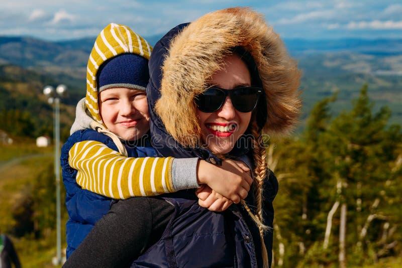 Den lyckliga kvinnan rymmer hennes son på henne baksida arkivfoto