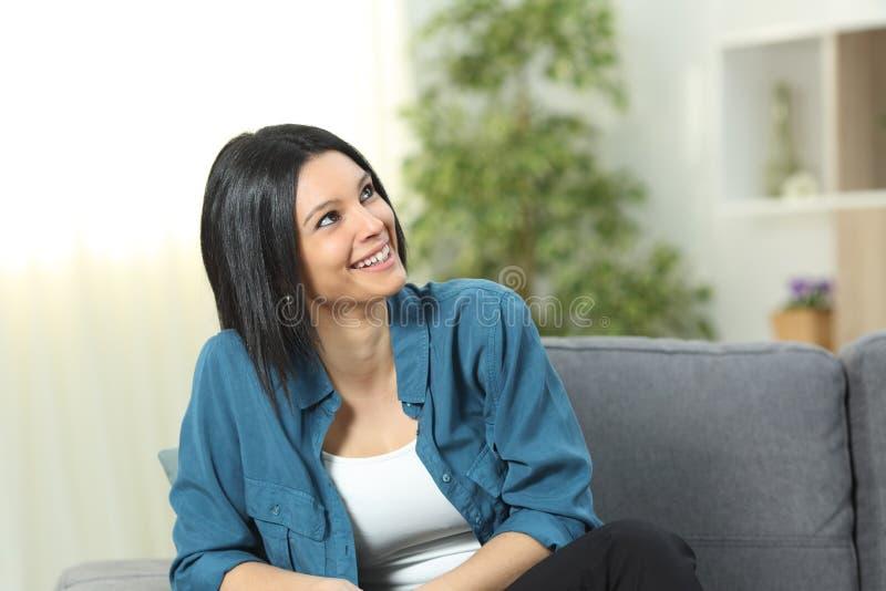 Den lyckliga kvinnan ser ovanf?r att sitta p? en soffa hemma royaltyfri foto