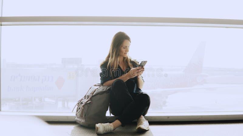 Den lyckliga kvinnan sitter med smartphonen vid flygplatsfönstret Caucasian flicka med ryggsäcken genom att använda budbäraren ap royaltyfri fotografi