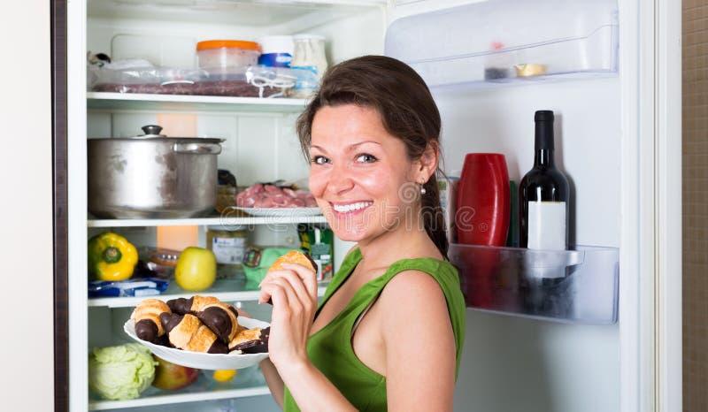 Den lyckliga kvinnan som äter kakor, near kylskåpet royaltyfri fotografi