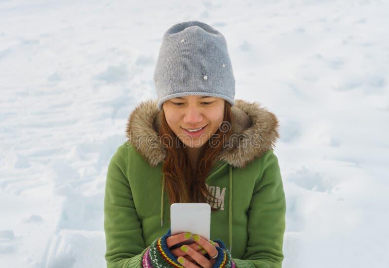 Den lyckliga kvinnan som använder mobiltelefonen på, skidar fältet arkivbilder