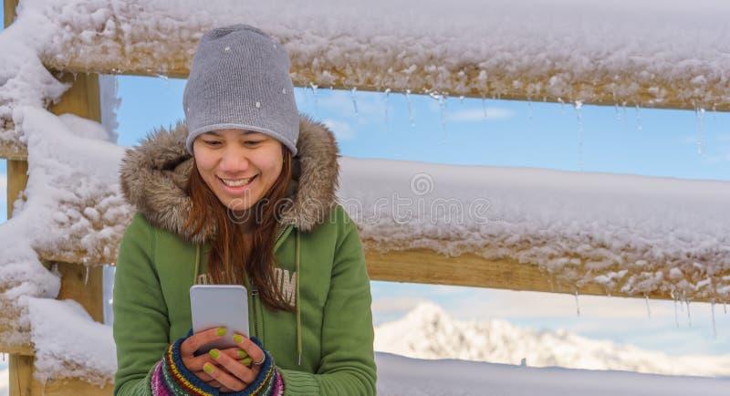 Den lyckliga kvinnan som använder mobiltelefonen på, skidar fältet nära trästaketet royaltyfri bild
