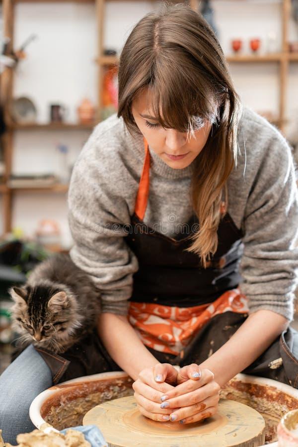 Den lyckliga kvinnan som arbetar på keramiker, rullar i krukmakeriseminarium Familjeföretag shoppar hugger krukan från lerasiktsö arkivbilder