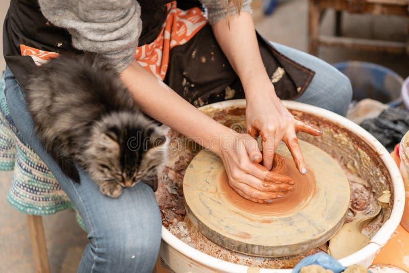 Den lyckliga kvinnan som arbetar på keramiker, rullar i krukmakeriseminarium Familjeföretag shoppar hugger krukan från lerasiktsö royaltyfri bild