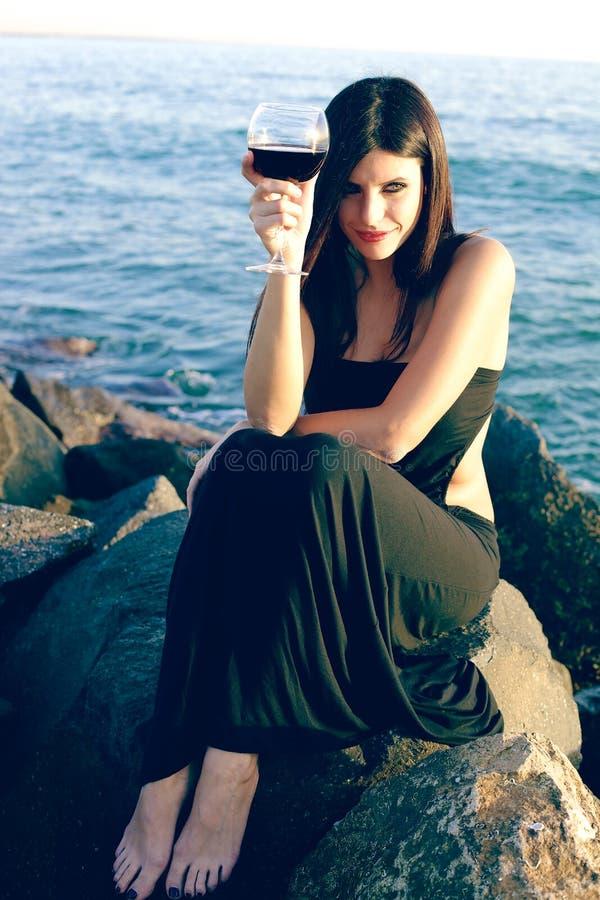 Den lyckliga kvinnan som festar på, vaggar framme av havet med rött vin arkivfoton