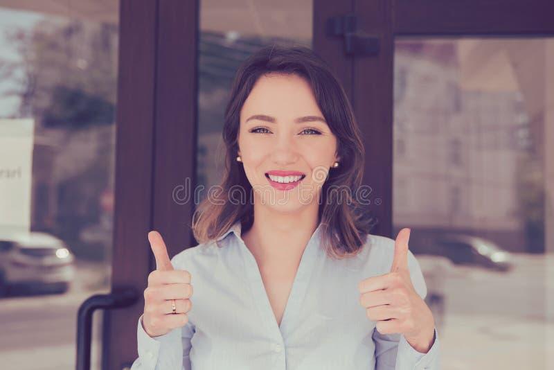 Den lyckliga kvinnan som ger tummar gör en gest upp, anseende utanför den nya lägenhetskomplexet arkivfoto