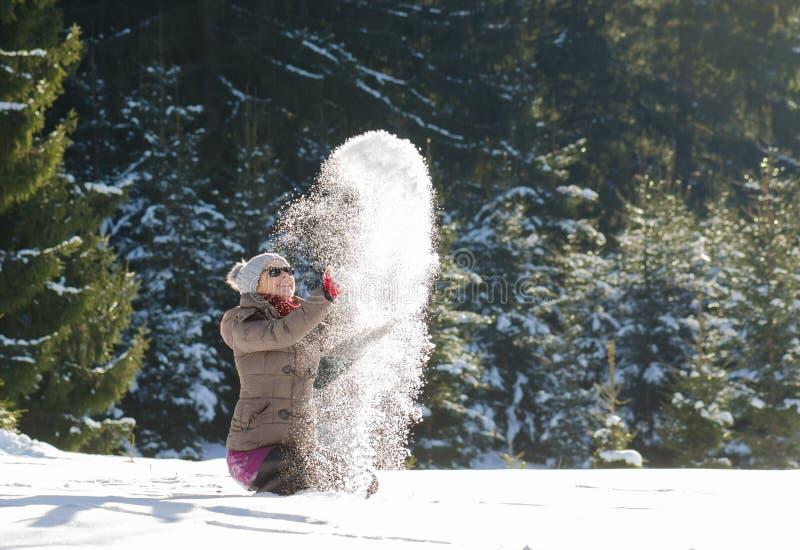 Den lyckliga kvinnan som har gyckel i snökast, kastar snöboll ovanför henne arkivfoto