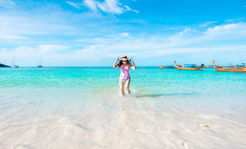 Den lyckliga kvinnan som kör stranden, och havet har ljus himmel för feriesommarför koppla av och lopp royaltyfri bild