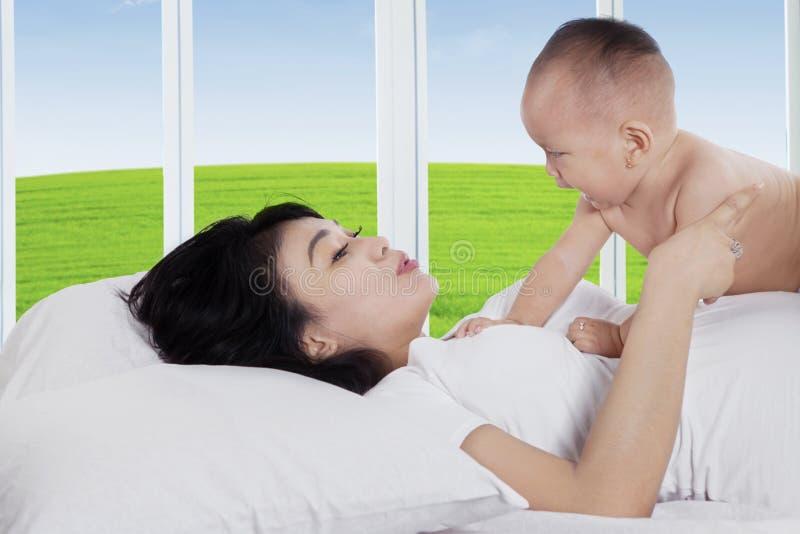 Den lyckliga kvinnan som spelar med, behandla som ett barn på säng arkivbilder