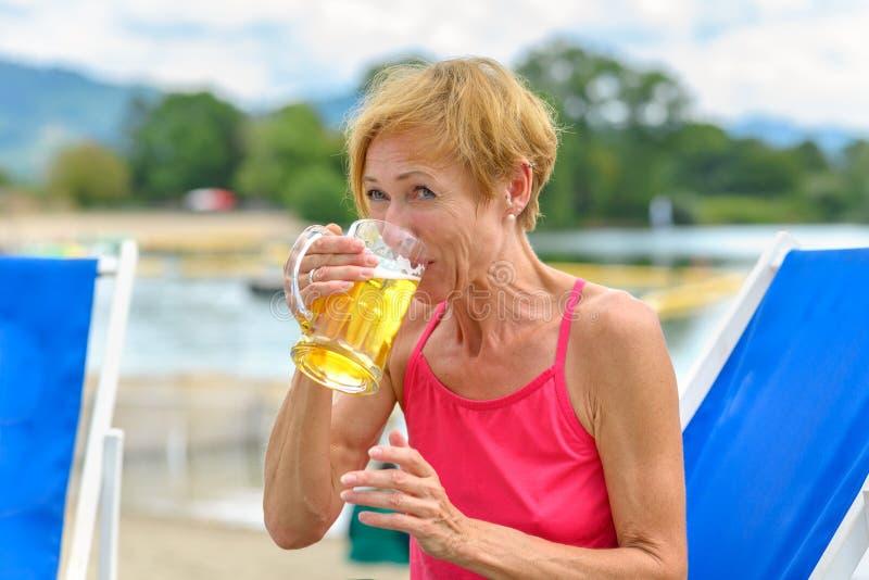 Den lyckliga kvinnan som tycker om ett iskallt, rånar av öl fotografering för bildbyråer