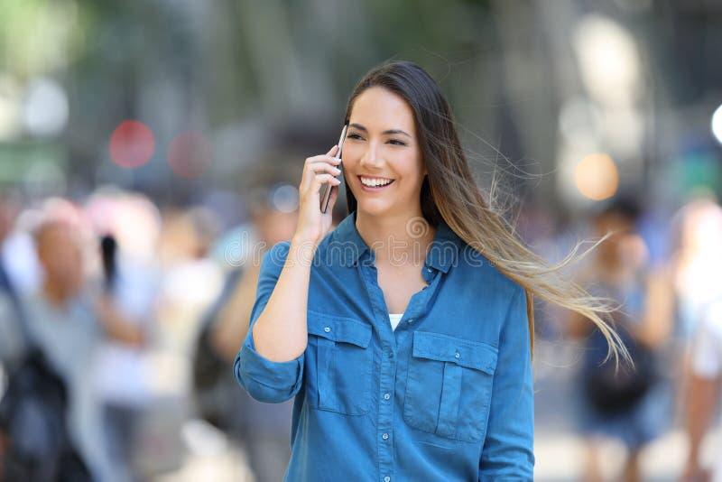 Den lyckliga kvinnan talar på telefonen i gatan royaltyfri bild