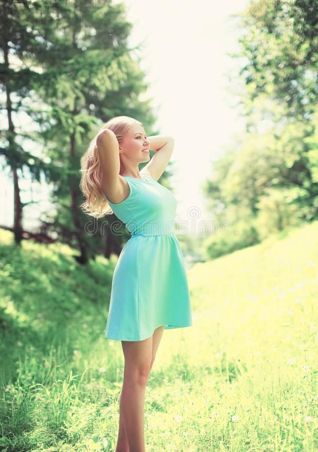 Den lyckliga kvinnan tycker om solig dag i skog royaltyfria bilder