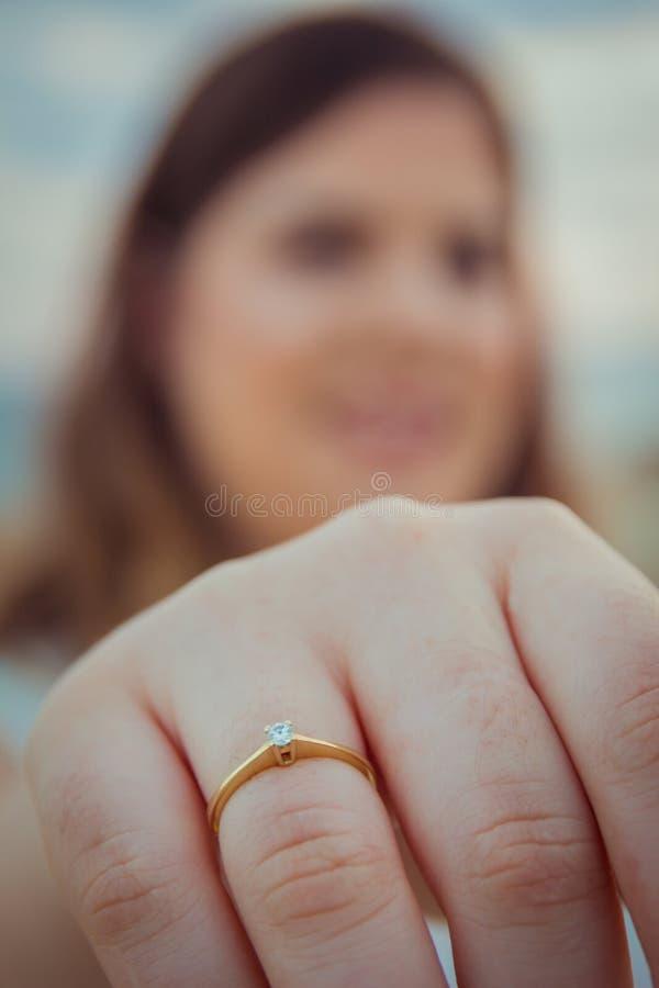 Den lyckliga kvinnan visar av hennes nya förlovningsring på hennes finger arkivfoton