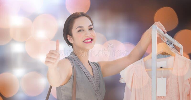 Den lyckliga kvinnavisningen tummar upp, medan shoppa över bokeh royaltyfri foto