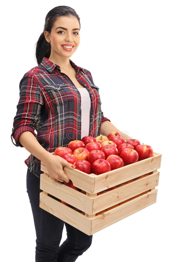 Den lyckliga kvinnliga bonden som rymmer träspjällådan, fyllde med äpplen royaltyfri bild