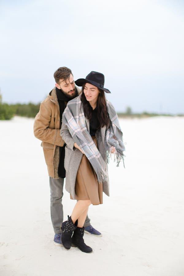 Den lyckliga kvinnliga personen och mannen med bärande lag och halsdukar för skägg som står i vinter, snöar bakgrund royaltyfria bilder