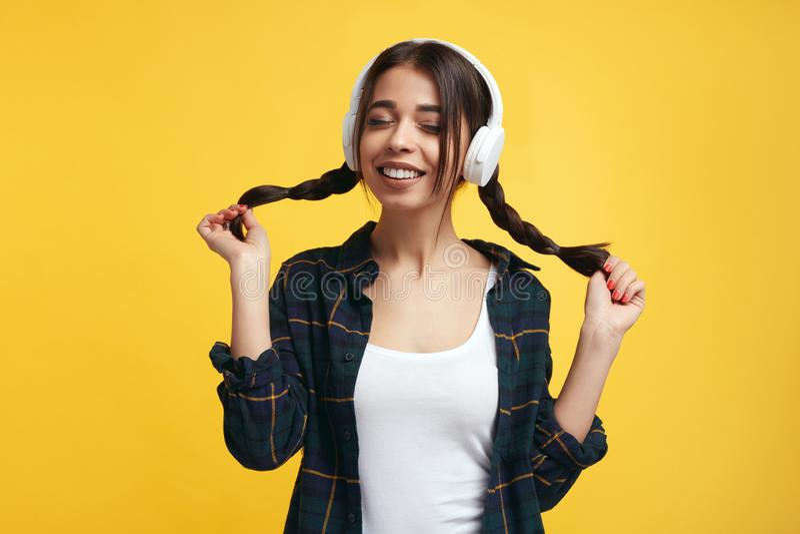 Den lyckliga kvinnliga ton?ringen tycker om ljudet av musik, rymmer hennes ponnysvansar, st?nger ?gon fr?n n?je, lyssnar s?ngen o fotografering för bildbyråer