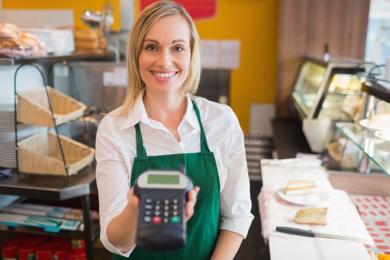 Den lyckliga kvinnlign shoppar den hållande kreditkortavläsaren för ägaren royaltyfri bild