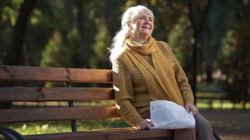 Den lyckliga läsningtidningen för den gamla kvinnan som sitter på bänk i, parkerar, pensionsåldern arkivfoto