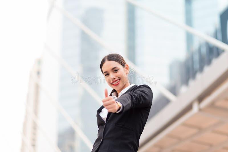 Den lyckliga le affärskvinnan med tummar gör en gest upp arkivfoto