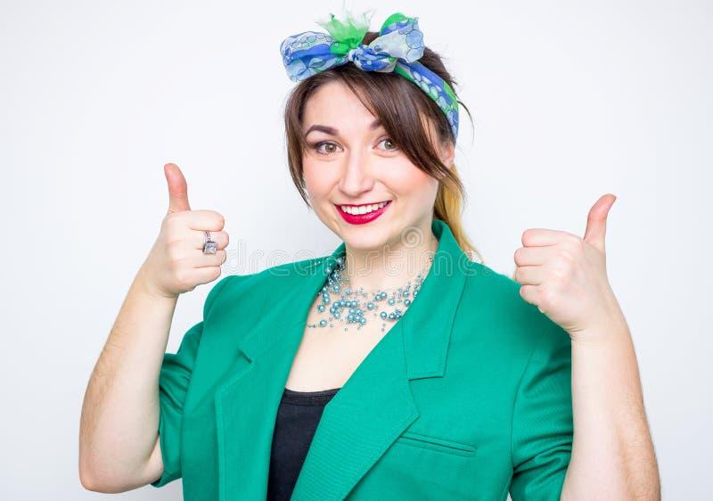 Den lyckliga le affärskvinnan som bär i grönt omslag med tummar gör en gest upp royaltyfria foton