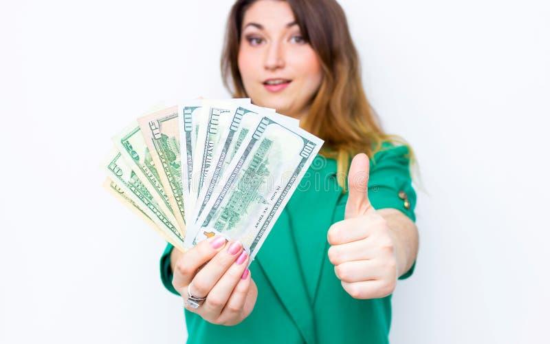 Den lyckliga le affärskvinnan som bär i grönt omslag med tummar gör en gest upp, och pengar Toppen lycklig upphetsad framgång för royaltyfria foton