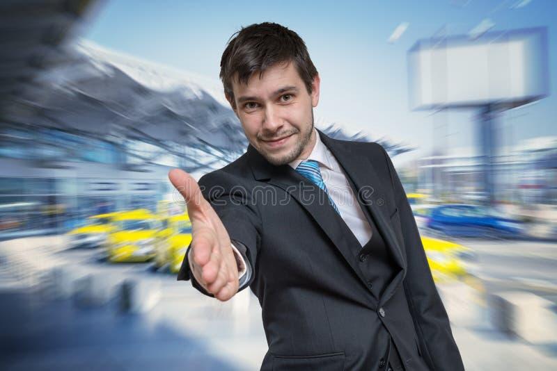 Den lyckliga le affärsmannen erbjuder handen för handskakning Inbjudan- och avtalsbegrepp royaltyfria bilder