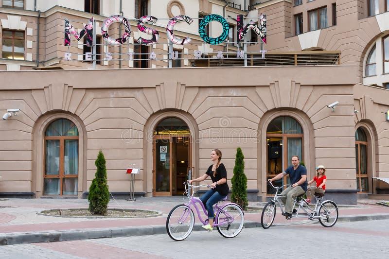 Den lyckliga le Caucasian familjen av fadern, modern och dottern har utomhus- cykelritt på sommar på hotellbyggnadsbakgrund royaltyfria bilder