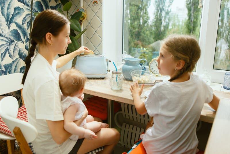 Den lyckliga le caucasian familjen i köket som förbereder frukosten arkivfoto