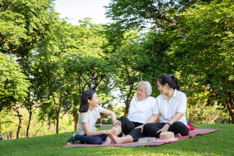 Den lyckliga le familjen som sitter på mattt i utomhus-, parkerar, den asiatiska höga farmorhälerimassagen av sondottern, kopplar arkivfoto