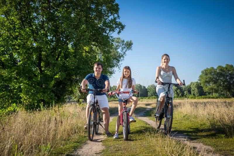 Den lyckliga le familjridningen cyklar på bygdvägen royaltyfria foton