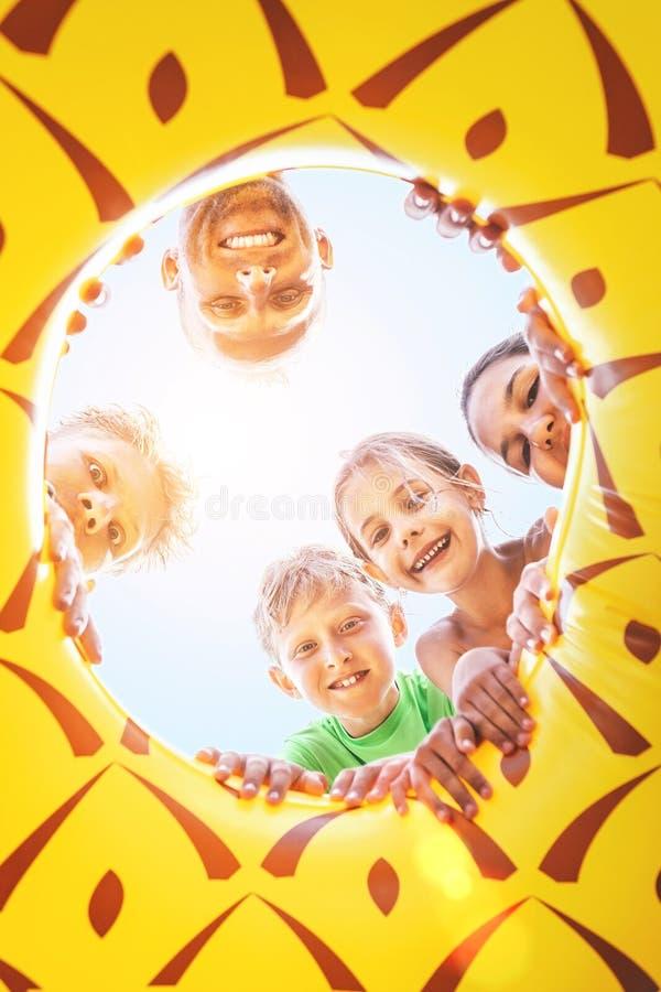 Den lyckliga le gruppen av childs, tonåret och det vuxna folket ser ner royaltyfria bilder