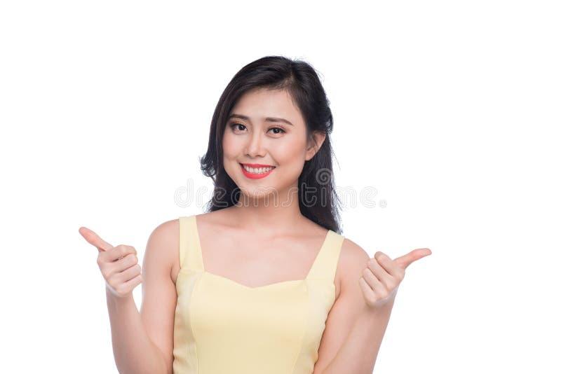 Den lyckliga le härliga unga asiatiska kvinnavisningen tummar upp mest gest royaltyfri bild