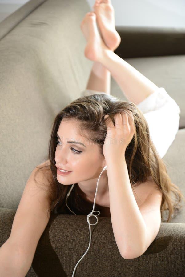 Den lyckliga le kvinnan lyssnar musik med hörlurar arkivbild