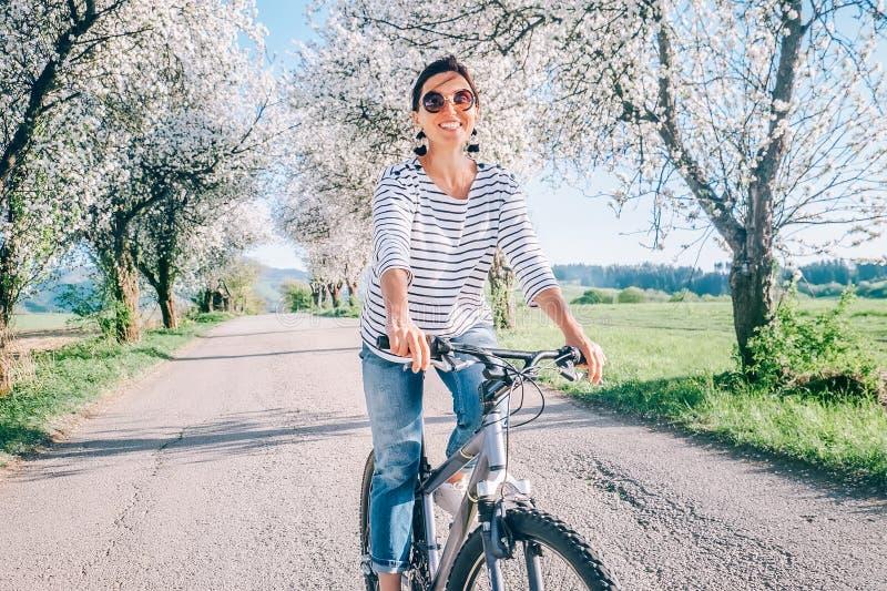 Den lyckliga le kvinnan rider en cykel på landsvägen under blomningträd Våren är den kommande begreppsbilden arkivbild