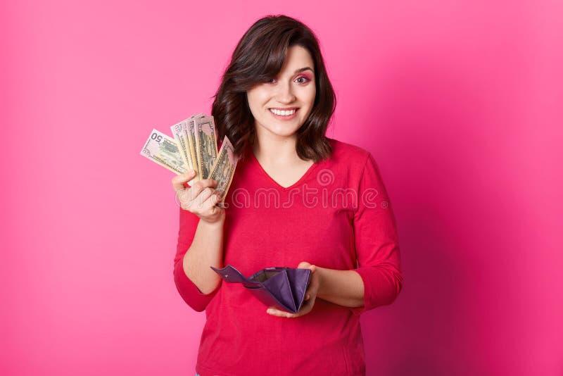 Den lyckliga le kvinnan rymmer plånboken, och pengar i händer, tänker hur man spenderar hennes lön Härlig brunettflicka som är gl arkivfoton