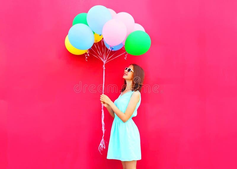 Den lyckliga le kvinnan ser på färgrika ballonger för en luft som har gyckel över rosa bakgrund royaltyfria foton