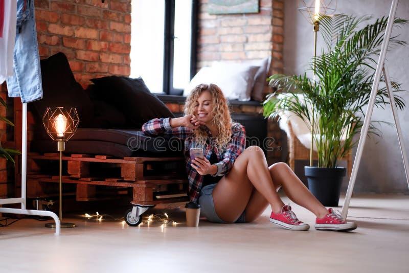 Den lyckliga le kvinnan sitter bredvid palettsoffan och rymmer hennes smartphone arkivfoton