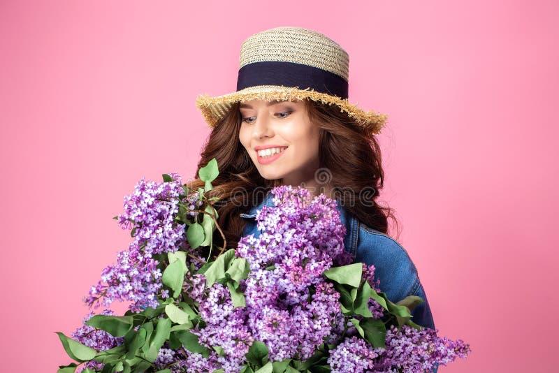 Den lyckliga le kvinnan som tycker om lukten av bukettlilan, blommar över arkivfoto
