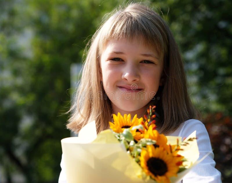 Den lyckliga le lilla flickan rymmer en bukett av solrosor royaltyfria bilder