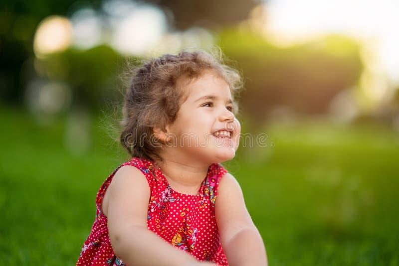 Den lyckliga le lilla flickan som sitter på gräs parkerar in, med den röda klänningen royaltyfri fotografi