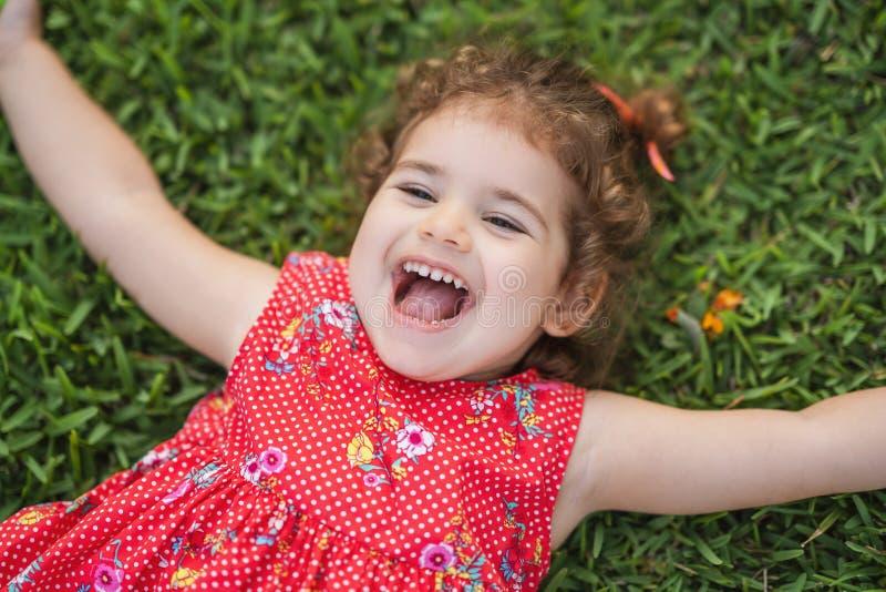 Den lyckliga le lilla litet barnflickan som lägger på gräs parkerar in, med den röda klänningen arkivbilder