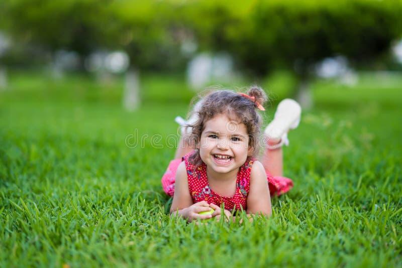 Den lyckliga le lilla litet barnflickan som lägger på gräs parkerar in, med den röda klänningen royaltyfri bild