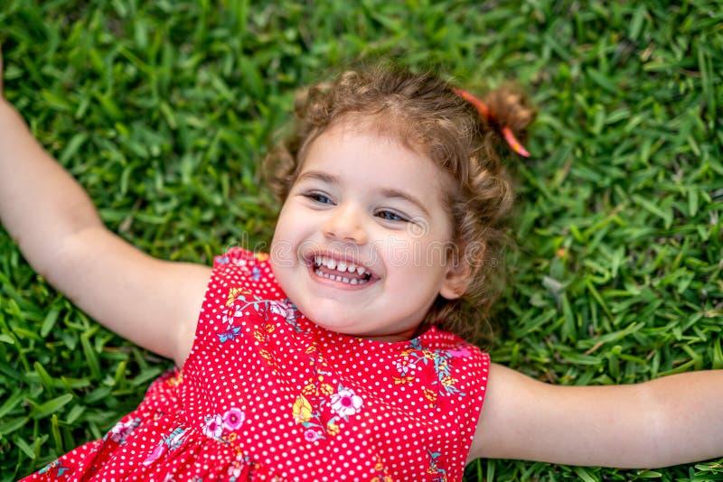 Den lyckliga le lilla litet barnflickan som lägger på gräs parkerar in, med den röda klänningen arkivfoton