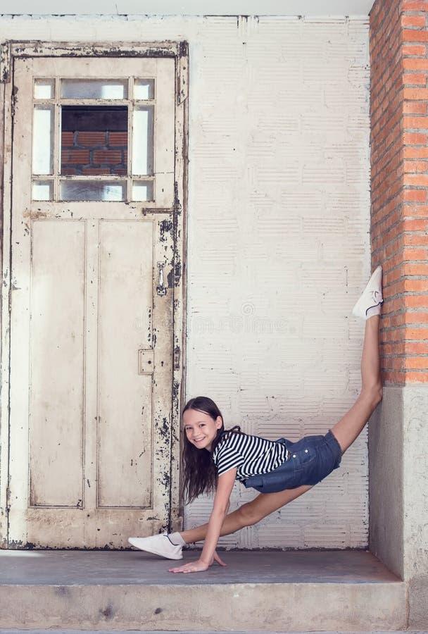 Den lyckliga le preteenflickan gör gymnastik i dörröppningen bredvid gammal trädörr i tegelsten och betongvägg Utomhus- dans royaltyfri bild