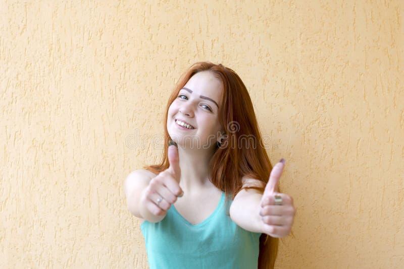 Den lyckliga le rödhåriga kvinnavisningen tummar upp arkivbilder