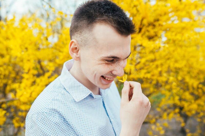 Den lyckliga le romantiska unga mannen med vårguling blommar på trädgården arkivbild